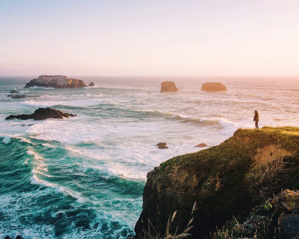 woman standing near edge of cliff looking over ocean