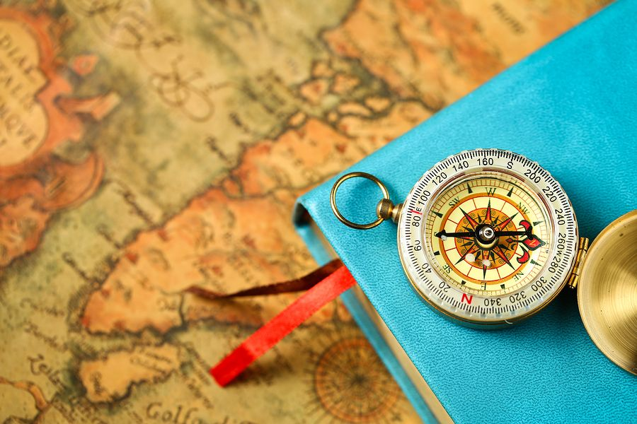 close up view of Compass and book on vintage old map background