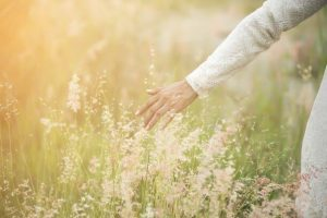 woman wearing white dress,releasing hand and touching the grass; concept of letting go
