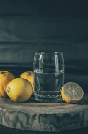 a glass half full of water surround by lemons, representing the glass half-full/half-empty concept
