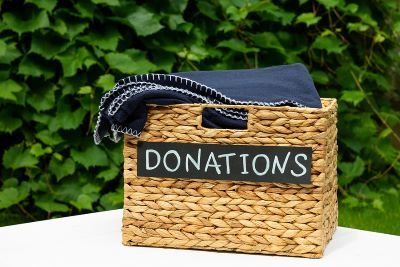 "Woven square basket labeled ""donations""; set against a background of greenery"