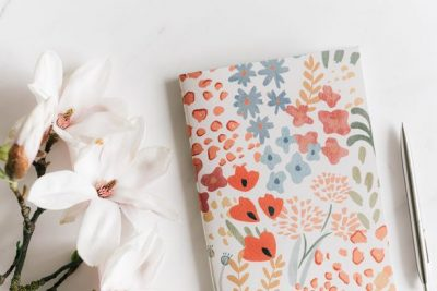 White flowers next to notebook with pastel watercolor floral design and silver pen