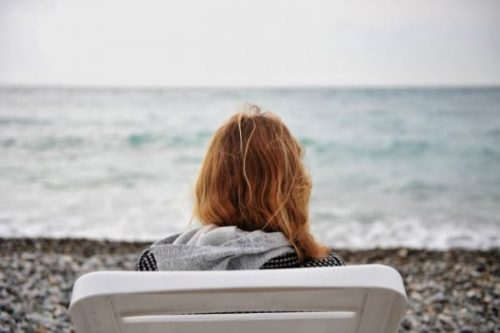 Lonely woman sitting on the shore overlooking the ocean
