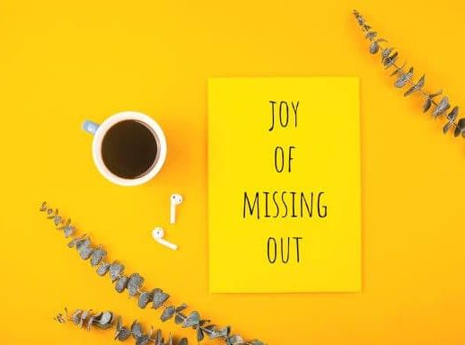 Joy of Missing Out written on yellow paper with eucalyptus and a cup of coffee nearby