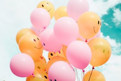Pink and yellow balloons with happy faces and frowns set against a blue sky